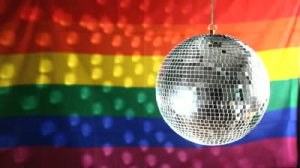 stock-footage-disco-ball-revolving-against-gay-pride-flag-with-light-reflection-1